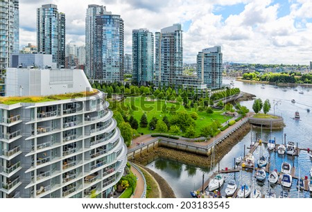 Vancouver aerial close view of the skyline of glass towers and waterfront park of green grassy lawn and trees along a marina with boats - stock photo