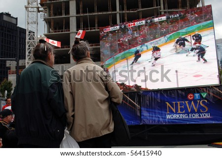 VANCOUVER, BC, CANADA - JULY 01: Canadians are watching rerun of 2010 Winter Olympics final hockey game Canada VS USA  during Canada Day festivities on July 01, 2010 in Vancouver, BC, Canada - stock photo