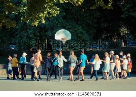 Vancouver BC Canada,July 8,2018.group of people holding hands dancing in the basketball playground