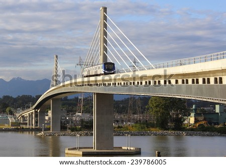 VANCOUVER, BC/CANADA JUNE 24 2014: Rapid transit as a tram crosses the Fraser Bridge from Vancouver to Richmond. - stock photo