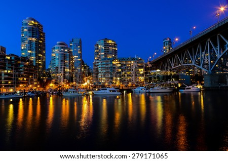 Vancouver BC Canada Skylines next to Granville Bridge along False Creek at Night. Vancouver is the third most populous metropolitan area and is the most ethnically diverse cities in Canada. - stock photo