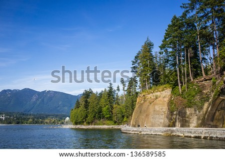 VANCOUVER, CANADA - APRIL 25, 2013: Unidentified people walk on seawall in Stanley Park on April 25, 2013. Seawall is 8.8-kilometer paved route that loops around the park.