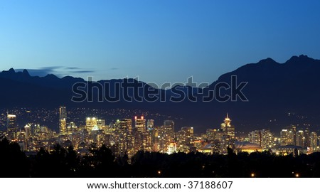 Vancouver Canada at night set in between the trees and the North Shore mountains. - stock photo