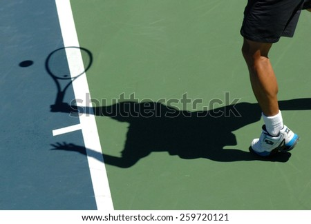 VANCOUVER, CANADA - AUGUST 7, 2014: An athlete casts a shadow during tennis match in Stanley Park in Vancouver, Canada, on August 7, 2014. - stock photo