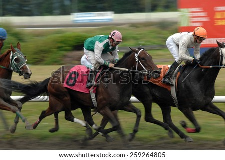VANCOUVER, CANADA - AUGUST 6, 2012: Horses ridden by jockeys compete at Hastings Park racecourse in Vancouver, Canada, on August 6, 2012. - stock photo