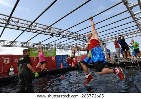 VANCOUVER, CANADA - AUGUST 17, 2014: Runners take part in the annual Concrete Hero obstacle race to raise funds in support of life-saving cancer research in Vancouver, Canada, on August 17, 2014. - stock photo