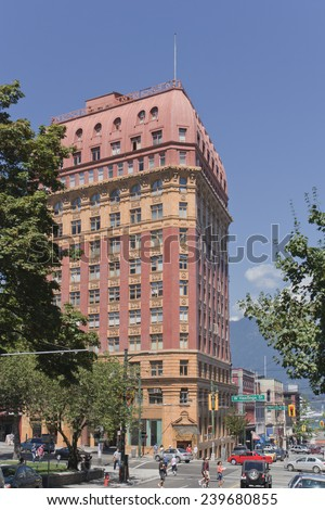 VANCOUVER, CANADA - AUGUST  6, 2005: Street Scene with traffic around the Dominion Building in West Hastings Street. The Dominion Building is a commercial building and located on the edge of Gastown.  - stock photo