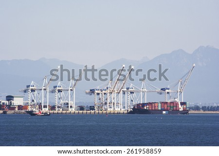 VANCOUVER, CANADA - AUGUST 4, 2005: Vancouver Harbor with Containers and a Dock Crane loading a Container Ship. The Port of Vancouver is the largest port in Canada.