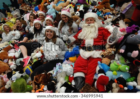 VANCOUVER, CANADA - DECEMBER 13, 2013: Santa Claus poses with the pile of plushies donated during a Christmas charity toy drive event in Vancouver, Canada, Dec. 13, 2013. - stock photo