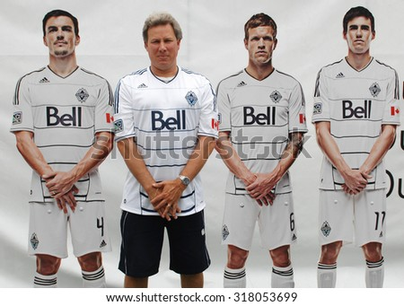 VANCOUVER, CANADA - JULY 22, 2012: A soccer fan poses with Vancouver Whitecaps FC players' cutouts outside of BC Place in Vancouver, Canada, July 22, 2012.