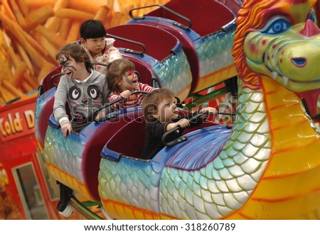 VANCOUVER, CANADA - MARCH 16, 2013: Kids enjoy the ride at the PlayDome, a carnival-style amusement park, in Vancouver, Canada, Mar.16, 2013. - stock photo