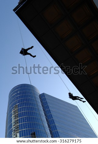 VANCOUVER, CANADA - SEPTEMBER 10, 2014: A man climbs down office building during Easter Seals Drop Zone fundraiser to benefit children with disabilities in Vancouver, Canada, on September 10, 2014.