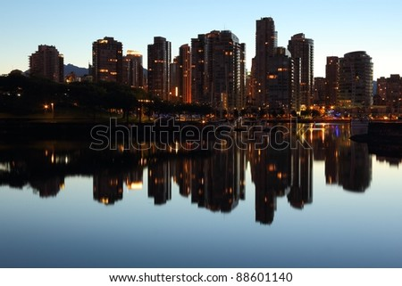 Vancouver condominiums and office towers at morning twilight behind Granville Island reflecting in the still water of False Creek. British Columbia, Canada. - stock photo