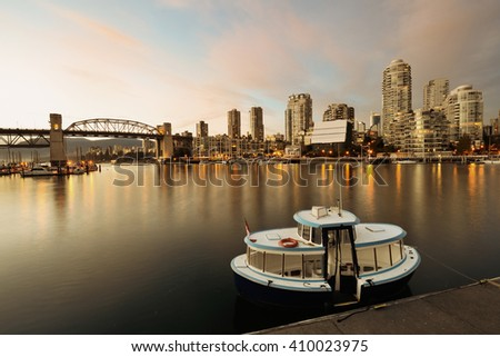 Vancouver False Creek at sunset with bridge and boat. - stock photo