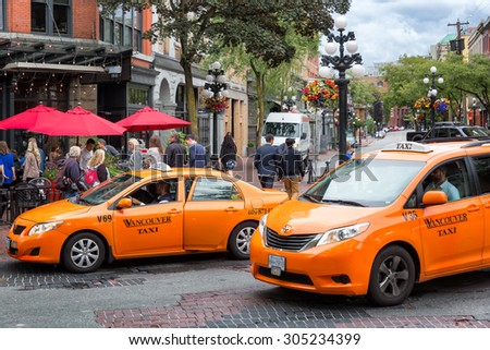 VANCOUVER-JUN 27, 2014: Orange taxis pull up in Vancouver's trendy Gastown historic district, known for restaurants, nightlife, galleries and upscale shops. Popular with locals and tourists. - stock photo