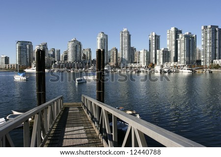 Vancouver skyline from Granville Island seen across from a dock - stock photo