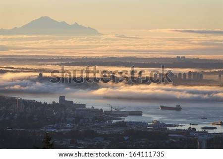 Vancouver Sunrise Fog. A high angle view of Vancouver and the Burrard Inlet at sunrise. Mount Baker, in Washington State, rises in the distance. British Columbia, Canada. - stock photo