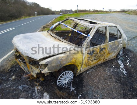 Vandalised car lies abandoned by side of road - stock photo