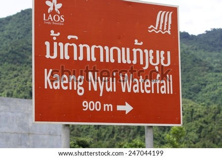 VANG VIENG, LAOS - AUGUST 11: A bright red sign showing the way to Kaeng Nyui Waterfall on the roadside near the town of Vang Vieng, Laos on the 11th August, 2014.