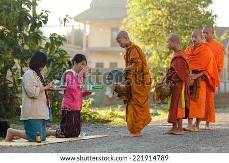 VANG VIENG, LAOS, MARCH 19, 2011: women giving daily food at the Buddhist monks during early morning traditional alms in the village of Viang Vieng, Laos - stock photo