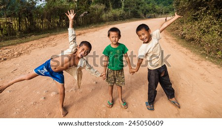 VANG VIENG, LAOS - NOVEMBER 9, 2013 : Unidentified kids posing on a road in Vang Vieng, Laos on November 9, 2013. Vang Vieng is a tourism-oriented town in Laos popular among young foreign tourists. - stock photo