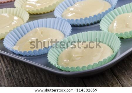 vanilla cake batter in a cupcake baking tin before baking - stock photo