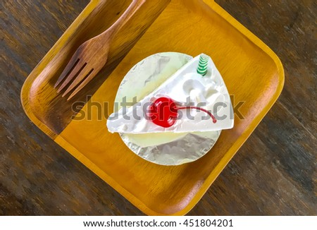 Vanilla cake placed on a wooden plate viewed from the top. - stock photo