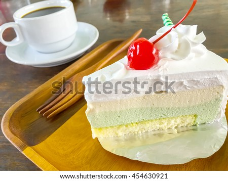 Vanilla cake placed on a wooden plate with a cup of coffee. - stock photo