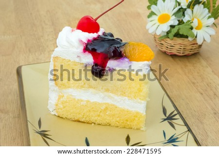 Vanilla cake topping with cherry, orange, Blueberry