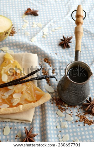 Vanilla coffee in the traditional cezve with a piece of pear cake, decorated with almond and vanilla pod - stock photo