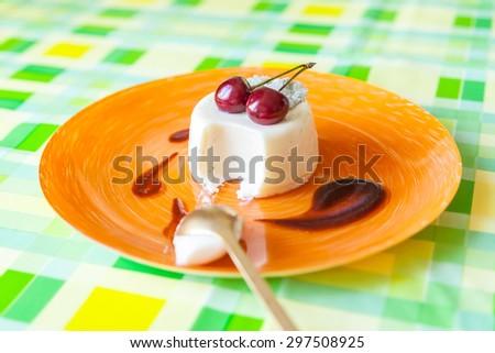 Vanilla creamy panna cotta with cherries on orange plate - stock photo