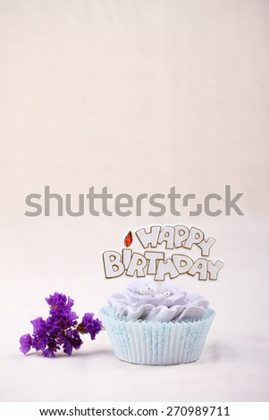 vanilla cupcake frosting with buttercream, flower shape, decorated with happy birthday label - stock photo