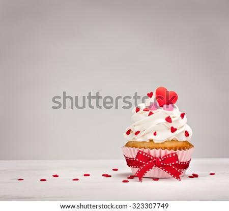 Vanilla Cupcake with buttercream icing, heart shaped sprinkles and a red bow. - stock photo