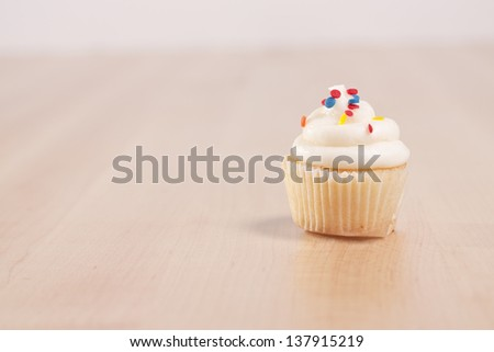 Vanilla cupcake with frosting and colorful sprinkles