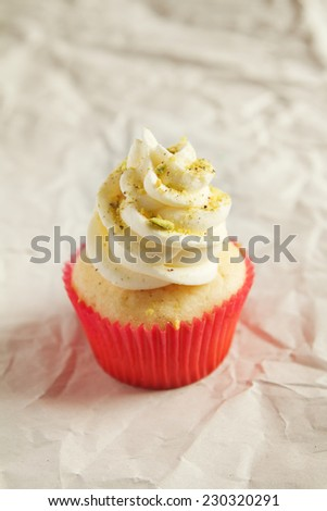 Vanilla cupcake with pistachio sprinkles with clear space - stock photo