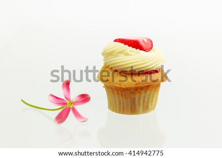 Vanilla Cupcake with Strawberry on top and flower on white background - stock photo