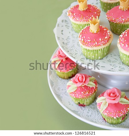 Vanilla cupcakes decorated with fondant roses. Copyspace to the left.