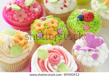 Vanilla cupcakes with buttercream icing and various decorations - stock photo