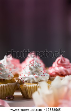 Vanilla cupcakes with pink and white cream, dark background, candy bars, text space, selective focus, close up