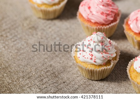 Vanilla cupcakes with white and pink cream, concrete background, text space, selective focus, close up - stock photo