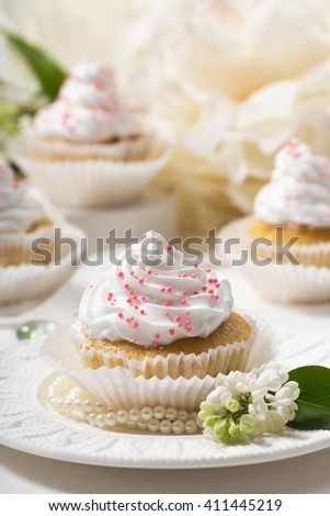 Vanilla cupcakes with white cream on a white table,white flower and leaf, lilac, selective focus, close up - stock photo