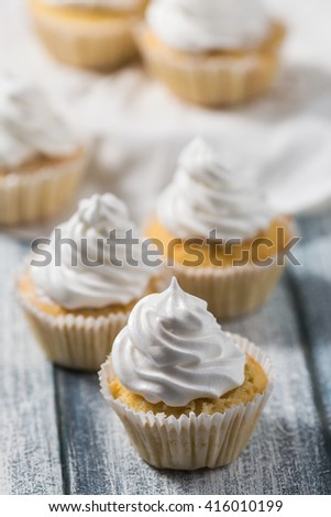 Vanilla cupcakes with white cream on wooden table, whipped cream, selective focus - stock photo