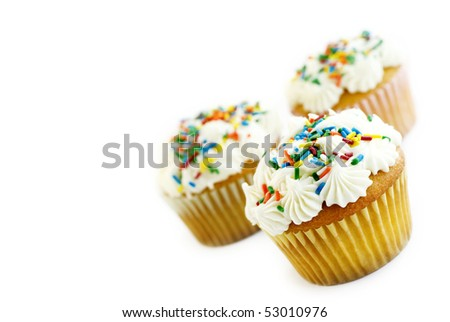 Vanilla Cupcakes with white frosting and colored sprinkles tilted in corner with selective focus, isolated on white background with copy space - stock photo