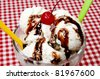 Vanilla ice cream and spoons with cherry and chocolate fudge topping on table with red gingham table cloth. - stock photo