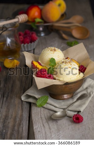 Vanilla ice cream ball with fresh peach and raspberry on moody rustic wooden table top. - stock photo