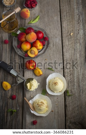 Vanilla ice cream ball with fresh peach and raspberry on moody rustic wooden table top. Overhead view. - stock photo