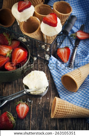 Vanilla Ice Cream in a waffle cones with fresh strawberries - stock photo