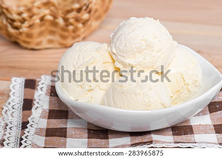Vanilla ice cream in white bowl with waffles on the wooden background