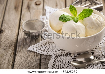 Vanilla ice cream with mint leaves in white bowl on rustic wooden background, selective focus, copy space - stock photo