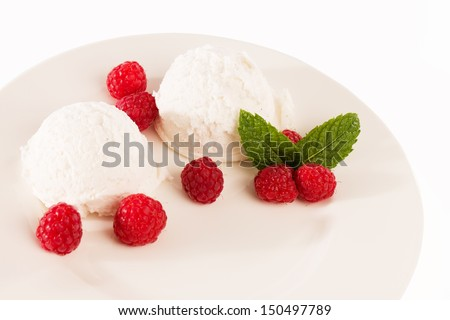 vanilla ice cream with raspberries and mint on a fawn plate from top on white - stock photo
